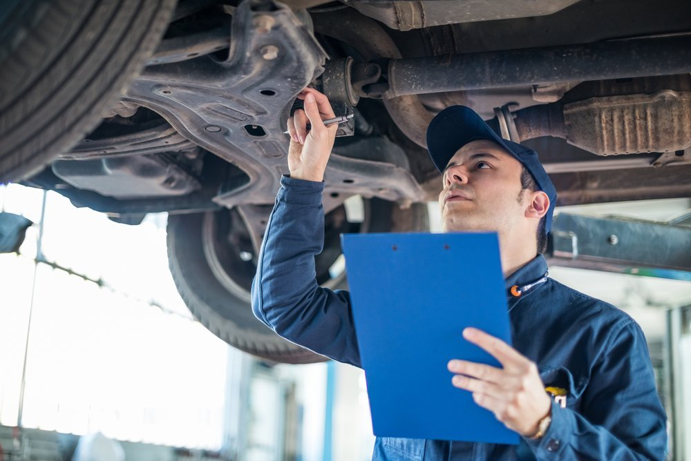 Man Inspecting Car Components | Auto Body Repair in Sioux Falls